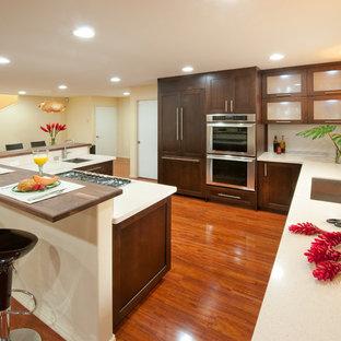 ハワイの大きいトロピカルスタイルのおしゃれなL型キッチン (アンダーカウンターシンク、シェーカースタイル扉のキャビネット、濃色木目調キャビネット、人工大理石カウンター、白いキッチンパネル、パネルと同色の調理設備、無垢フローリング、アイランドなし、茶色い床) の写真