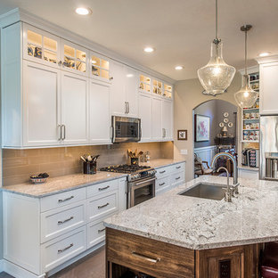 Traditional kitchen ideas - Inspiration for a timeless galley kitchen remodel in Other with an undermount sink, shaker cabinets, white cabinets, gray backsplash, stainless steel appliances and an island