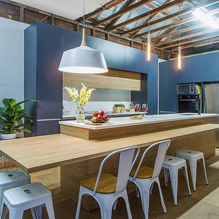 Design ideas for a large modern galley open plan kitchen in Central Coast with a submerged sink, flat-panel cabinets, blue cabinets, laminate countertops, white splashback, ceramic splashback, stainless steel appliances, plywood flooring and an island.