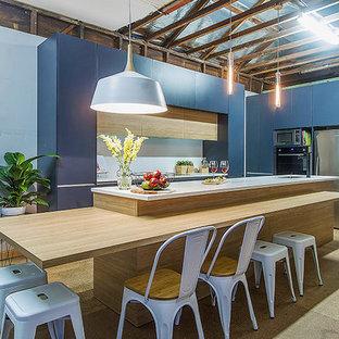 セントラルコーストの広いモダンスタイルのおしゃれなキッチン (アンダーカウンターシンク、フラットパネル扉のキャビネット、青いキャビネット、ラミネートカウンター、白いキッチンパネル、セラミックタイルのキッチンパネル、シルバーの調理設備、合板フローリング) の写真