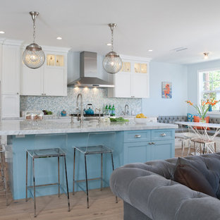 Large coastal eat-in kitchen ideas - Example of a large beach style l-shaped medium tone wood floor eat-in kitchen design in Los Angeles with a farmhouse sink, shaker cabinets, white cabinets, blue backsplash, mosaic tile backsplash, stainless steel appliances, an island and marble countertops
