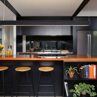 This is an example of a mid-sized contemporary galley open plan kitchen in Brisbane with an integrated sink, flat-panel cabinets, black cabinets, wood benchtops, stainless steel appliances, concrete floors, multiple islands, mirror splashback and grey floor.