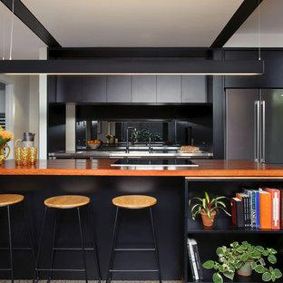 Idéer för ett mellanstort modernt kök, med en integrerad diskho, släta luckor, svarta skåp, träbänkskiva, rostfria vitvaror, betonggolv, flera köksöar, spegel som stänkskydd och grått golv