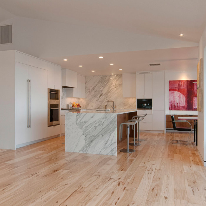 Example of a large trendy light wood floor, beige floor and vaulted ceiling eat-in kitchen design in Denver with an undermount sink, flat-panel cabinets, white cabinets, marble countertops, white back