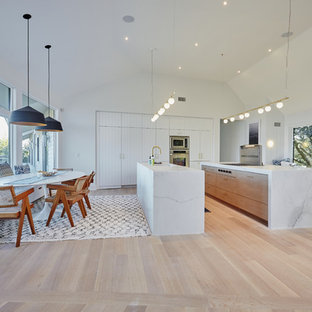 This is an example of a contemporary l-shaped eat-in kitchen in Other with louvered cabinets, stainless steel appliances, light hardwood floors, multiple islands and beige floor.
