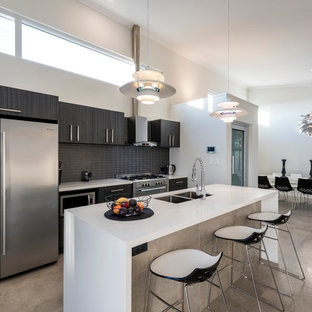 Mid-sized contemporary galley open plan kitchen in Perth with an undermount sink, flat-panel cabinets, dark wood cabinets, solid surface benchtops, ceramic splashback, stainless steel appliances, ceramic floors, with island, grey floor and black splashback.