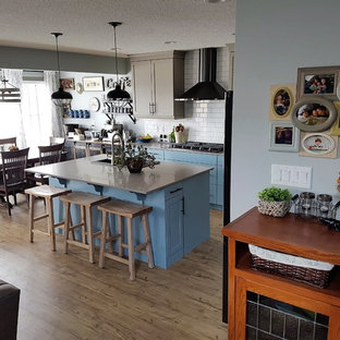 Photo of a mid-sized transitional eat-in kitchen in Edmonton with a double-bowl sink, shaker cabinets, blue cabinets, quartzite benchtops, white splashback, black appliances, vinyl floors, with island and grey benchtop.