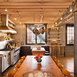 Ejemplo de cocina urbana con fregadero sobremueble y electrodomésticos de acero inoxidable