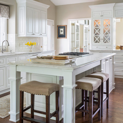 Inspiration for a large timeless u-shaped dark wood floor eat-in kitchen remodel in Minneapolis with an undermount sink, white cabinets, white backsplash, subway tile backsplash, an island, raised-panel cabinets and granite countertops