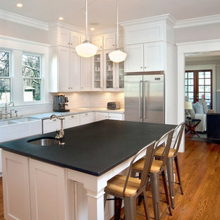 Traditional enclosed kitchen appliance - Elegant l-shaped medium tone wood floor enclosed kitchen photo in Atlanta with a farmhouse sink, shaker cabinets, white cabinets, white backsplash, subway tile backsplash, stainless steel appliances and an island
