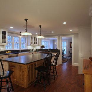 Modelo de cocina en L, clásica, grande, abierta, con fregadero sobremueble, armarios estilo shaker, puertas de armario blancas, encimera de esteatita, electrodomésticos de acero inoxidable, suelo de madera en tonos medios y una isla