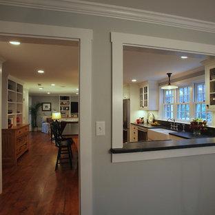 Ejemplo de cocina en L, clásica, grande, abierta, con fregadero sobremueble, armarios estilo shaker, puertas de armario blancas, encimera de esteatita, electrodomésticos de acero inoxidable, suelo de madera en tonos medios y una isla
