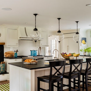 Large transitional eat-in kitchen ideas - Large transitional l-shaped medium tone wood floor and brown floor eat-in kitchen photo in Boston with a farmhouse sink, flat-panel cabinets, white cabinets, soapstone countertops, white backsplash, subway tile backsplash, paneled appliances and an island