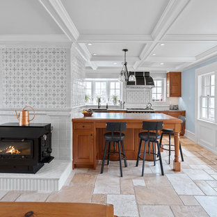 Large traditional enclosed kitchen designs - Inspiration for a large timeless limestone floor and multicolored floor enclosed kitchen remodel in Philadelphia with a farmhouse sink, raised-panel cabinets, medium tone wood cabinets, granite countertops, multicolored backsplash, porcelain backsplash, black appliances, a peninsula and blue countertops
