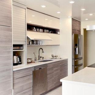 Immagine di una cucina minimalista di medie dimensioni con lavello sottopiano, ante lisce, ante in legno chiaro, top in quarzo composito, elettrodomestici in acciaio inossidabile e isola