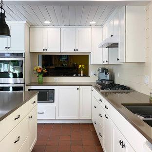 ボストンの中サイズのトラディショナルスタイルのおしゃれなキッチン (アンダーカウンターシンク、落し込みパネル扉のキャビネット、白いキャビネット、人工大理石カウンター、ベージュキッチンパネル、木材のキッチンパネル、シルバーの調理設備の、テラコッタタイルの床、赤い床、茶色いキッチンカウンター) の写真