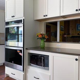 ボストンの中サイズのおしゃれなキッチン (アンダーカウンターシンク、落し込みパネル扉のキャビネット、白いキャビネット、人工大理石カウンター、ベージュキッチンパネル、木材のキッチンパネル、シルバーの調理設備の、テラコッタタイルの床、赤い床、茶色いキッチンカウンター) の写真