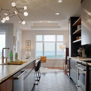 他の地域の大きいモダンスタイルのおしゃれなキッチン (ダブルシンク、フラットパネル扉のキャビネット、グレーのキャビネット、クオーツストーンカウンター、緑のキッチンパネル、セラミックタイルのキッチンパネル、シルバーの調理設備の、セラミックタイルの床、グレーの床、白いキッチンカウンター) の写真