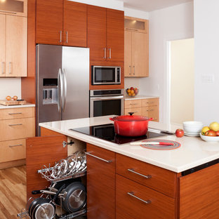 Large contemporary l-shaped eat-in kitchen in DC Metro with medium hardwood floors, with island, flat-panel cabinets, medium wood cabinets, white splashback and stainless steel appliances.