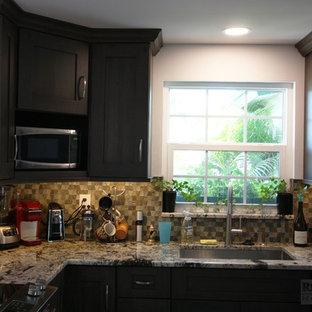 Cette image montre une petite cuisine américaine chalet en L avec un évier encastré, un placard à porte shaker, des portes de placard en bois sombre, un plan de travail en granite, une crédence multicolore, une crédence en mosaïque, un électroménager en acier inoxydable, un sol en vinyl, un sol marron et un plan de travail multicolore.