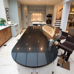 This is an example of a mid-sized contemporary l-shaped eat-in kitchen in DC Metro with an undermount sink, recessed-panel cabinets, blue cabinets, soapstone benchtops, grey splashback, glass tile splashback, stainless steel appliances, marble floors, multiple islands and white floor.