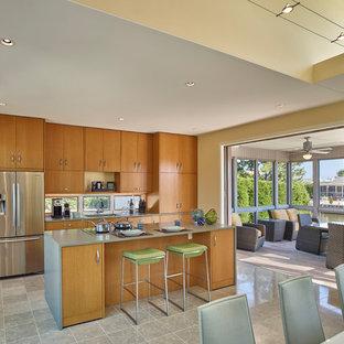 ニューヨークのビーチスタイルのおしゃれなキッチン (シングルシンク、フラットパネル扉のキャビネット、中間色木目調キャビネット、シルバーの調理設備の、グレーの床、グレーのキッチンカウンター) の写真