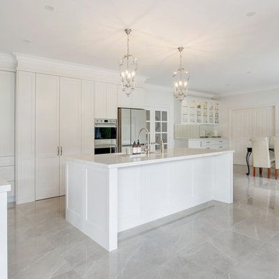 Example of a large classic l-shaped porcelain tile and brown floor open concept kitchen design in Sydney with an undermount sink, shaker cabinets, beige cabinets, quartz countertops, gray backsplash, stone slab backsplash, stainless steel appliances, an island and white countertops