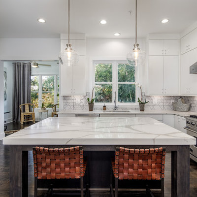 Transitional u-shaped dark wood floor and brown floor kitchen photo in Atlanta with an undermount sink, flat-panel cabinets, white cabinets, gray backsplash, stainless steel appliances, an island and white countertops