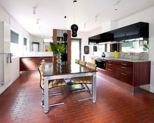 Example Of A Minimalist Eat In Kitchen Design In Hampshire With Flat Panel Cabinets