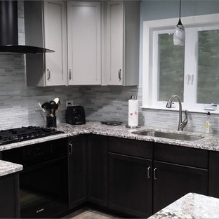 Medium sized traditional u-shaped open plan kitchen in Boston with a submerged sink, shaker cabinets, black cabinets, granite worktops, grey splashback, glass tiled splashback, stainless steel appliances, slate flooring, an island and grey floors.