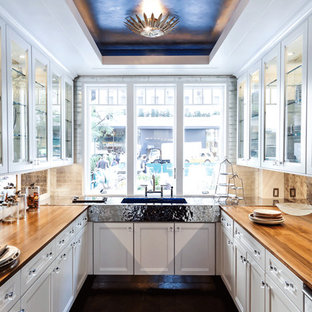 Example of a classic kitchen design in New York with wood countertops, glass-front cabinets, white cabinets and an integrated sink