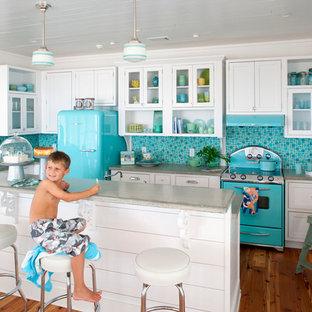 Ispirazione per una cucina a L costiera con ante di vetro, ante bianche, top in cemento, paraspruzzi multicolore, paraspruzzi con piastrelle a mosaico, elettrodomestici colorati, pavimento in legno massello medio e isola