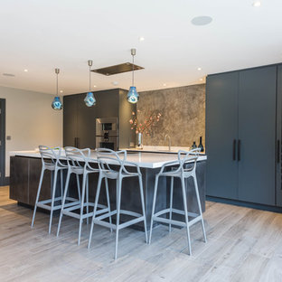 Inspiration for a medium sized contemporary single-wall kitchen in Kent with a submerged sink, flat-panel cabinets, grey splashback, integrated appliances, an island, beige floors, white worktops and blue cabinets.