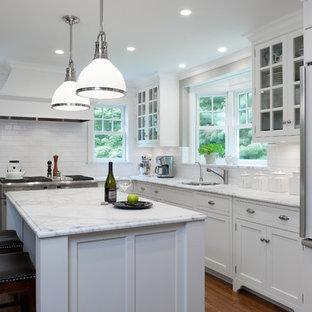 ニューヨークのトラディショナルスタイルのおしゃれなL型キッチン (アンダーカウンターシンク、シェーカースタイル扉のキャビネット、白いキャビネット、白いキッチンパネル、サブウェイタイルのキッチンパネル、パネルと同色の調理設備) の写真