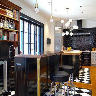 Small eclectic l-shaped eat-in kitchen in Calgary with a farmhouse sink, recessed-panel cabinets, marble benchtops, black splashback, ceramic splashback, stainless steel appliances, white cabinets, medium hardwood floors and with island.