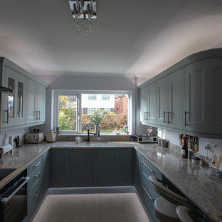 This is an example of a small contemporary u-shaped enclosed kitchen in Other with a belfast sink, shaker cabinets, beige cabinets, granite worktops, green splashback, ceramic splashback, integrated appliances, ceramic flooring, a breakfast bar, grey floors and beige worktops.