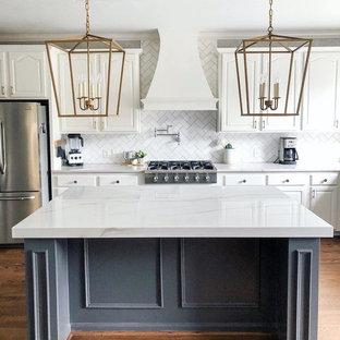 Einzeilige, Große Country Küche mit profilierten Schrankfronten, weißen Schränken, Marmor-Arbeitsplatte, Küchenrückwand in Weiß, Rückwand aus Metrofliesen, Küchengeräten aus Edelstahl, braunem Holzboden, Kücheninsel, braunem Boden und weißer Arbeitsplatte in Raleigh