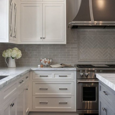 Inspiration for a contemporary dark wood floor and brown floor kitchen remodel in Raleigh with an undermount sink, recessed-panel cabinets, white cabinets, marble countertops, gray backsplash, subway tile backsplash, stainless steel appliances, an island and multicolored countertops