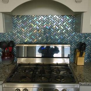 Modelo de cocina comedor minimalista, grande, con puertas de armario blancas, salpicadero azul, salpicadero de azulejos de vidrio, electrodomésticos de acero inoxidable y una isla