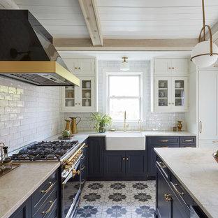 ニューヨークの地中海スタイルのおしゃれなキッチン (白いキッチンパネル、サブウェイタイルのキッチンパネル、エプロンフロントシンク、シェーカースタイル扉のキャビネット、青いキャビネット、パネルと同色の調理設備、マルチカラーの床、ベージュのキッチンカウンター) の写真