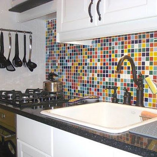 Bild på ett avskilt, litet eklektiskt linjärt kök, med en nedsänkt diskho, luckor med infälld panel, vita skåp, granitbänkskiva, flerfärgad stänkskydd, stänkskydd i glaskakel och svarta vitvaror