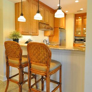 チャールストンの小さいビーチスタイルのおしゃれなキッチン (中間色木目調キャビネット、御影石カウンター、シルバーの調理設備の、無垢フローリング、ガラス扉のキャビネット、ベージュキッチンパネル、サブウェイタイルのキッチンパネル) の写真