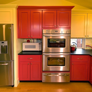This is an example of a contemporary kitchen in Seattle with recessed-panel cabinets, red cabinets, multi-coloured splashback, mosaic tile splashback and stainless steel appliances.