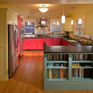 Modelo de cocina en U, actual, con fregadero bajoencimera, armarios con paneles empotrados, puertas de armario rojas, salpicadero multicolor, salpicadero con mosaicos de azulejos y electrodomésticos de acero inoxidable