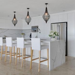 シドニーの中サイズのモダンスタイルのおしゃれなキッチン (フラットパネル扉のキャビネット、白いキャビネット、大理石カウンター、白いキッチンパネル、大理石の床、シルバーの調理設備の、セラミックタイルの床、茶色い床) の写真