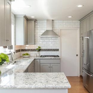 Kleine Klassische Wohnküche mit Doppelwaschbecken, Schrankfronten im Shaker-Stil, grauen Schränken, Granit-Arbeitsplatte, Küchenrückwand in Weiß, Rückwand aus Metrofliesen, Küchengeräten aus Edelstahl, braunem Holzboden und Halbinsel in San Francisco