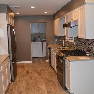 Стильный дизайн: параллельная, отдельная кухня среднего размера с фасадами в стиле шейкер, белыми фасадами, столешницей из переработанного стекла, коричневым фартуком, фартуком из стеклянной плитки, цветной техникой, врезной раковиной и полом из керамической плитки - последний тренд
