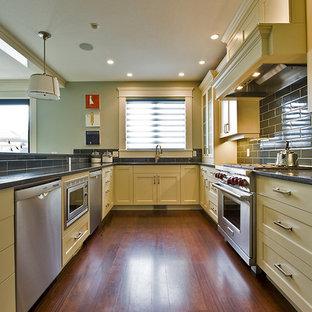 Imagen de cocina contemporánea con electrodomésticos de acero inoxidable, armarios con paneles empotrados, puertas de armario amarillas y salpicadero de azulejos tipo metro