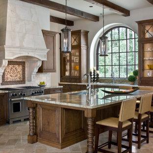 ヒューストンの大きい地中海スタイルのおしゃれなキッチン (アンダーカウンターシンク、ガラス扉のキャビネット、中間色木目調キャビネット、御影石カウンター、ベージュキッチンパネル、石タイルのキッチンパネル、パネルと同色の調理設備、トラバーチンの床) の写真