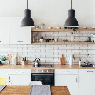 Ejemplo de cocina lineal, escandinava, pequeña, con armarios con paneles lisos, puertas de armario blancas, encimera de laminado, electrodomésticos negros, fregadero encastrado, salpicadero blanco, salpicadero de azulejos tipo metro y encimeras beige